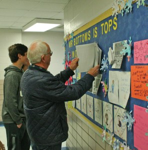 Kendra Peek/kendra.peek@amnews.com Tracie, Hayden and Harvey Bottoms look at artwork and stories from students about Ronnie Bottoms, beloved Perryville Elementary custodian, who is retiring after 21 years at the school.
