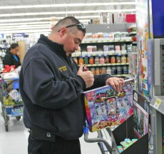 Kendra Peek/kendra.peek@amnews.com Danville Fire Lt. Shane Yocum looks at a toy for the Danville Fire Department Toy Drive.