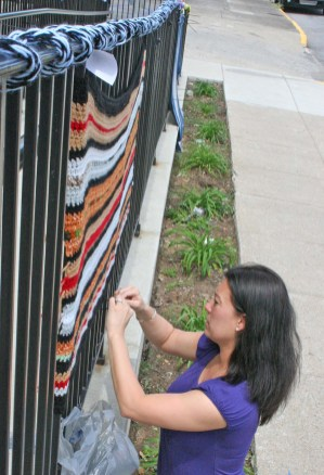 Kendra Peek/kendra.peek@amnews.com Danville High School Art Teacher Shelly Stinnett hangs a blanket outside the Community Arts Center as part of the All Wrapped Up project from her class.