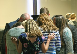 Kendra Peek/kendra.peek@amnews.com Staff from the Danville Christian Academy pray over Hannah Elise Brunner during the 2017 DCA graduation