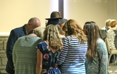 Kendra Peek/kendra.peek@amnews.com Staff from the Danville Christian Academy pray over Jenny Beth Cox during the 2017 DCA graduation