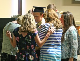 Kendra Peek/kendra.peek@amnews.com Staff members of the Danville Christian Academy pray over graduate James Tyler Mattingly after he received his diploma on Saturday. As each graduate departed the stage with their diploma, staff would gather around them to pray for their future path.