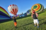 Laurent Nash of Stanford, right, carries his daughter, Hollie, 6, on his shoulders as they watch hot air balloons take off.