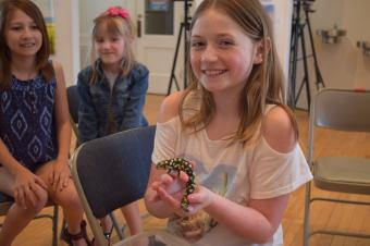 Margaux Tucker poses with a salamander while Gwyn Johnson and Lara Kate Sears look on.