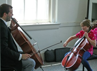 Kendra Peek/kendra.peek@amnews.com Luke Darville, left, and Anika Ellis, 9, right, during a cello lesson at Darville String Studio.