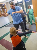 """Jacob Tamme """"dabs"""" with student Skylar Shewmaker in the hallway of Junction City Elementary."""