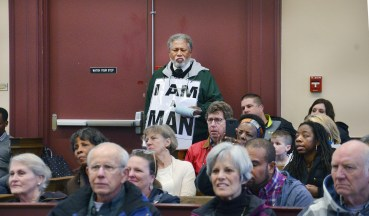 J.H. Atkins stands at the rear of the courtroom.