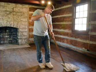 Tommy Lewis sweeps dust out of a window in the jail house cabin at Constitution Square Friday afternoon.