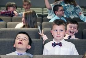 Before the Classical Conversations home school group began showing parents and families what they had learned, from left, Chase Bonner and Henry Sirasky wait in their seats as classmate Asher Sewell hams it up for the camera.