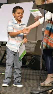 Jace Montgomer shakes hands with Melissa Sirasky after receiving a certificate.