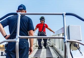Danville Firefighter Stephen Glovak climbs down the ladder truck's ladder after securing the flag.