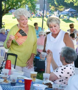 Jordi Moore fans herself with an old-fashioned patriotic fan as she and her friend, Karen Long talk to a new friend at the GABBF Great American Picnic Saturday evening.