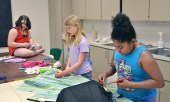 In a sewing class, Riley Russell, left works on an embroidery project while Moira Kelly cuts out the pattern for a skirt and Zaviera Simpson finishes a small pillow.