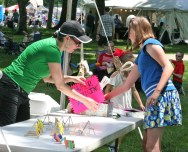 Kendra Peek/kendra.peek@amnews.com Lily Phillips, right, and her mom Kimberly, left, arrange Lily's paper quilling table at the Kids Art Fest during the Great American Brass Band Festival.