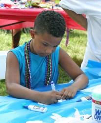 Kendra Peek/kendra.peek@amnews.com Landon Turner, 6, colors a mask in the kids' art area at the Great American Brass Band Festival.