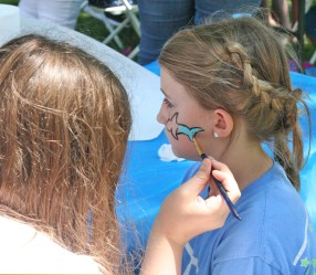 Kendra Peek/kendra.peek@amnews.com Mary Isola, left, paints a dolphin on the cheek of Kate Briese, 10, right.