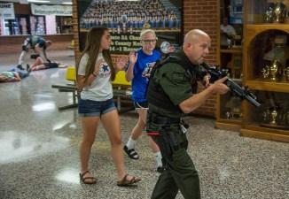 Ben Kleppinger/ben.kleppinger@amnews.com Boyle County Sheriff Derek Robbins escorts two students to safety.