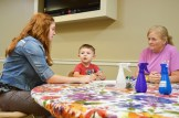 """Kinsey Hisle, from left, listens to Will Sledge, who came to the children's library to make tie-dyed backpacks with his grandmother, Carol Vance. Carol said she didn't know about the programs Kinsey leads as youth services librarian until they wondered in one day. """"He just loves it, we're definitely coming back,"""" Carol said."""