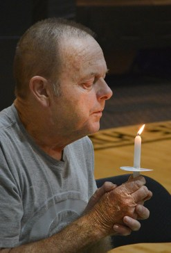 Photo by Robin Hart/robin.hart@amnews.com In recognition of International Overdose Awareness Day at Indian Hills Christian Church Thursday night, John Hughes holds a candle in remembrance of someone who died from a drug overdose.