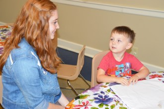 Kinsey talks with Will Sledge, 3, who came to her program with his grandmother, Carol Vance. Kinsey will sometimes join the kids as they participate in programs if they ask her to.