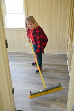 Photo by Robin Hart/robin.hart@amnews.com Mary Shultz uses a push broom to cleanup after the Lowe's crew had finished painint and laying a floor in a back room at the Gibson Cottage on Friday.