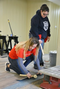 At left, Laura Clemons and Jessica Lewis, both volunteers from the Georgetown Lowe's, place flooring down at the Gibson Cottage.