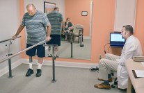 Conrad Hicks, of Junction City, tries walking on a new leg with a computerized knee as Casey Thomas talks to him about how the knee works