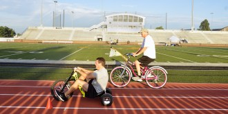 "President and CEO of Ephraim McDowell Health rides an adult-sized Big-wheel and Farmers National Bank CEO Greg Caudill takes a bike around the track at Centre College during the Heart of Kentucky United Way .5K ""race"" Friday morning."