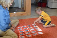 Elsea and Harper enjoying a learning activity involving cards with shapes and colors on them.