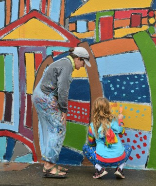 Photo by Robin Hart/robin.hart@amnews.com Contemporary mural artist Andee Rudloff, coaches Maya Wade as she paints on the mural Saturday