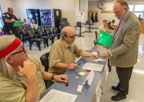 Ben Kleppinger/ben.kleppinger@amnews.com Danville City Manager Ron Scott, right, attempts to get some food from Northpoint inmates Troy Hunt, far left, and Harold Root, who were running the food bank and homeless shelter station.