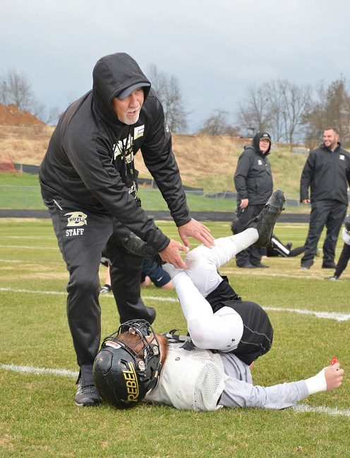 Boyle County High School head football coach Chuck Smith works with a player with a stretching drill.