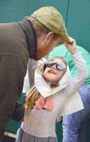 "Photo by Robin Hart/robin.hart@amnews.com Lyla Jackson gives her dad Matt Jackson's cap a tug after she performed with other kindergarten students at the annual ""Over the River"" performance at Woodlawn Elementary School Tuesday morning."