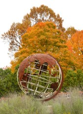 The large Earth sculpture in the parking lot of the Boyle County Library seems to be floating in place with spectacular orange trees in the background.