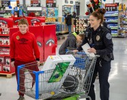 Ben Kleppinger/ben.kleppinger@amnews.com Danville Police Officer Ashleigh Koch, right, and 11-year-old Woodlawn student Ashton wait in line to check out.
