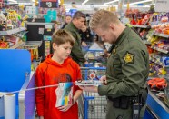 Ben Kleppinger/ben.kleppinger@amnews.com Boyle County Deputy Tanner Abbott and 12-year-old Boyle County Middle School student Steven examine a fishing rod at the checkout.
