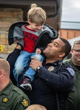 Ben Kleppinger/ben.kleppinger@amnews.com Danville Police Officer Paul Megilligan hoists his Shop with a Cop kid, 5-year-old Jansen, up on his shoulder for a group photo outside of Cheddar's.