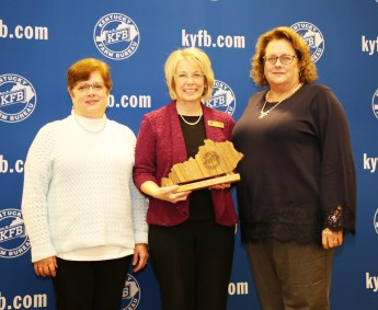 Jennifer Little and Terry Gilbert of the Boyle County Farm Bureau Women's Committee, accept the 2018 Gold Star Award of Excellence from Vicki Bryant, chair of the Kentucky Farm Bureau state Women's Committee. The award was presented during a November 30 recognition program at the 99th Kentucky Farm Bureau annual meeting.
