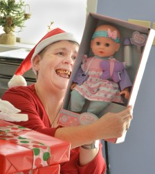 Robin Hart robin.hart@amnews.com Brenda Carey admires a baby doll she recieved for Christmas during a party at A Gathering Place Adult Day Health Care on Tuesday.