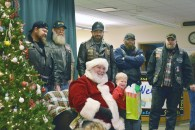 """Photo by Robin Hart/robin.hart@amnews.com Simon Cullen signs """"I love you"""" to his classmates and teachers at Kentucky School for the Deaf on Friday. He was sitting on Steve Brashear's lap who was dressed as Santa and was handing out gifts brought to the students by the Brothers Code Motorcycle Club."""