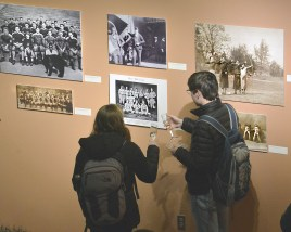 """Robin Hart/robin.hart@amnews.com Visitors celebrating Centre College's 200th anniversary Wednesday evening study historic photos from the college's past that are part of a photographic display titled """"Pieces of Time"""". The exhibit will be up through May 19."""