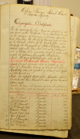 The original 1879 Organization Certificate for Farmers National Bank was discovered among the many ledgers that are stored in the bank's basement. The bank has worked from its location on Main Street since it began in 1879. Photo by Robin Hart