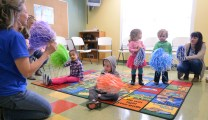 A group of 3-year-olds listen and dance as teacher Mary Wells, leads the fun. Photo by Robin Hart.