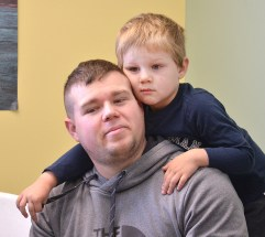 Hobie Daugherty sits during circle time as his son, Jase, leans over. Photo by Robin Hart.