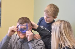Three-year-old Jase Daugherty peeks over his dad, Hobie Daugherty's shoulder as he tries on a paper scuba mask as his mom, Meghan watches.Photo by Robin Hart.