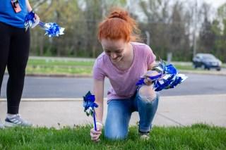 Boyle County High School Key Club member Amanda Cossentine plants a pinwheel. Photo by Ben Kleppinger.