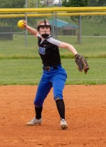 Shortstop Faith Breitenbach picks up a ground ball and throws to first base. Photo by Ben Kleppinger)