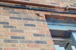 Just above the rear bay door of the central fire station, bricks are seen cracking due to the structural damage to the building. (Photo by Bobbie Curd)