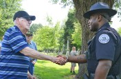 Danville Police officer Chad Bartleson, right, shakes hands with retired officer Charles Shannon following DPD memorial service for fallen officers in Bellevue Cemetery Friday afternoon. (Photo by Robin Hart)