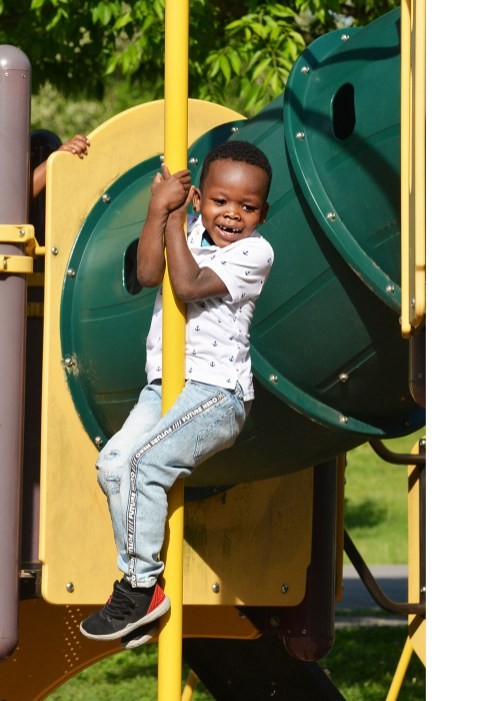 Hogsett Elementary School preschooler Tyran Gates II clings to a pole as slides down it at Millennium Park Tuesday morning. Photo by Robin Hart.